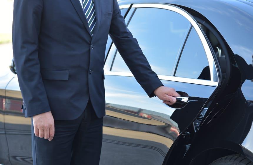 chauffeur opening limousine door for passanger