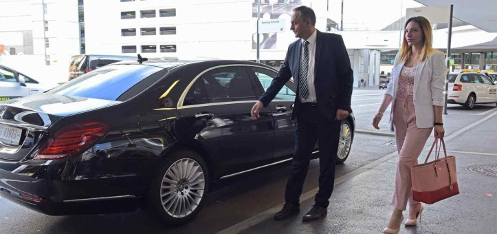 limousine service - chauffeur oppening car door - private transfers