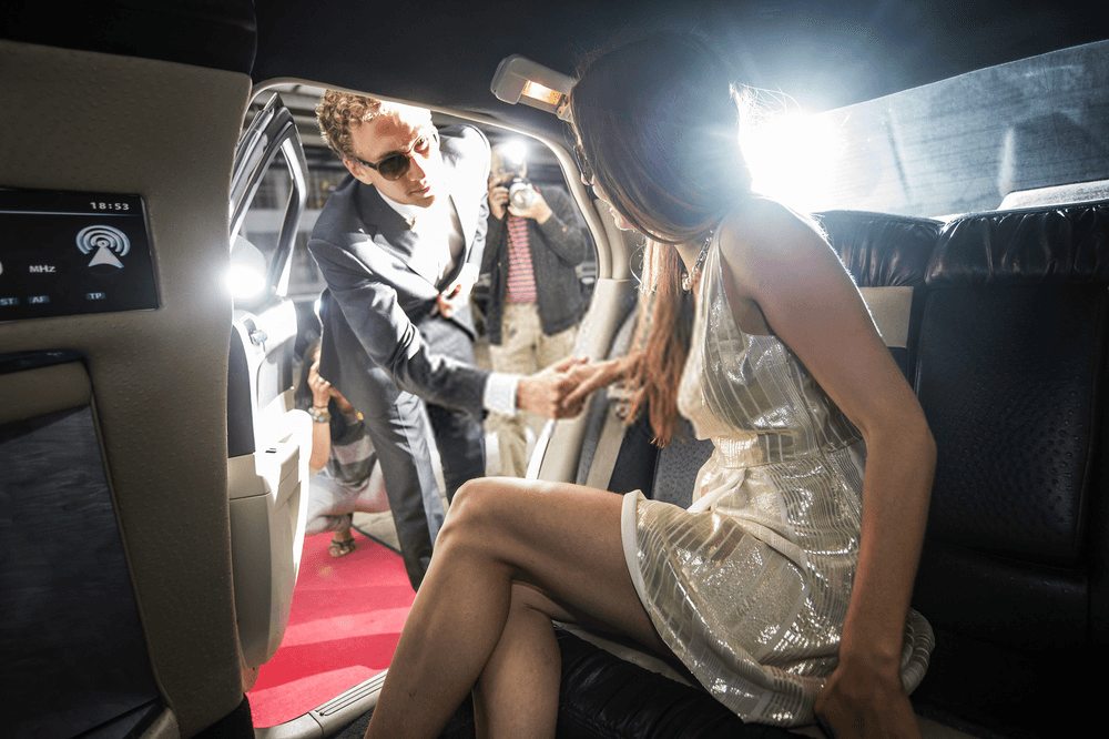 man helping lady out of a limo
