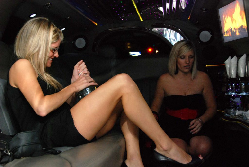 girls' night out in a limo - woman opening a bottle - two women in a limousine