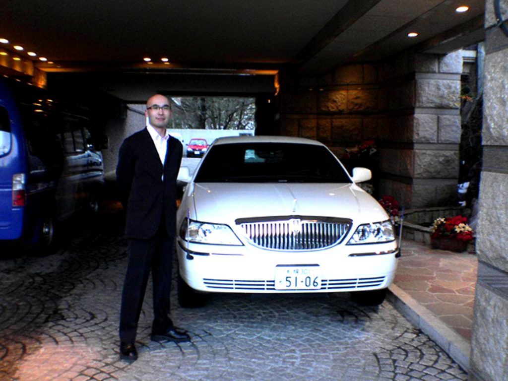 limousine and a chauffeur - chauffeur standing next to a limousine - white limo