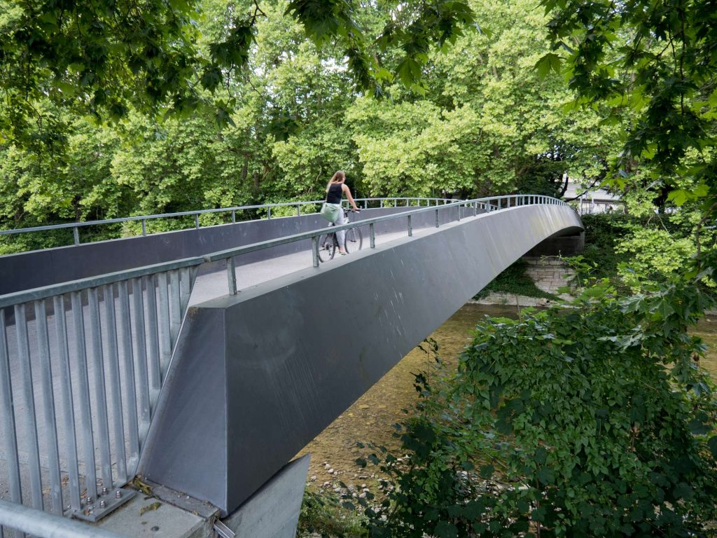 exciting things to do in zurich - cycling - woman cycling on a bridge