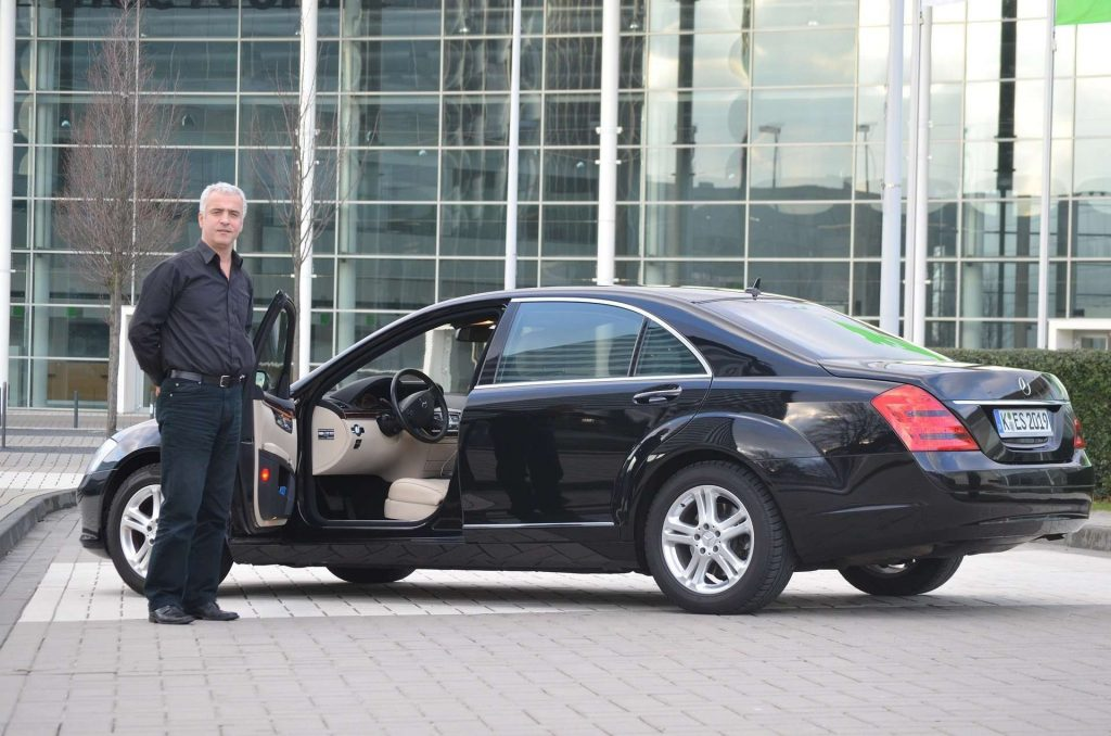 Airport transfer in a limo - limo airport transfer - chauffeur in front of a limo