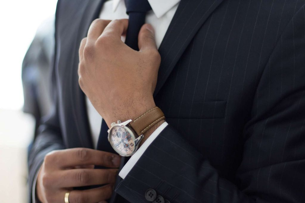chauffeur services - suit - wrist watch - tie - wedding band on a finger