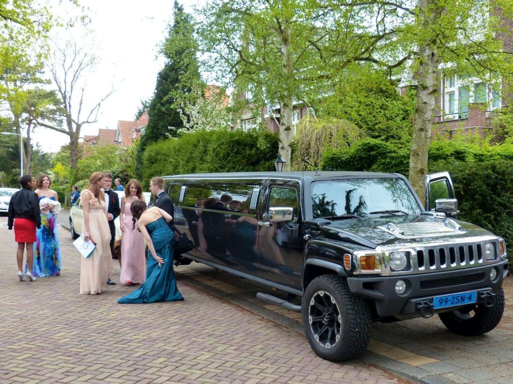 limo - prom - limousine service for prom - prom dresses - prom suits - teenagers in front of a limo